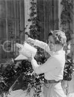 Woman watering plants in window boxes