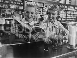 Girlfriends looking at magazine at soda fountain