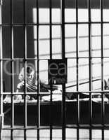 Woman through bars of jail cell