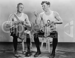 Two men knitting and sewing