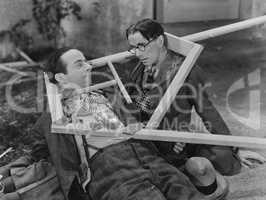 Wooden frame broken over two mens heads