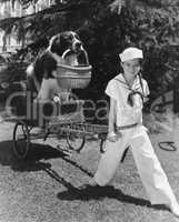 Girl in sailor suit pulling dog in basket