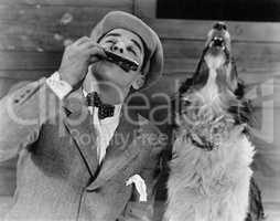 Man playing harmonica with howling dog