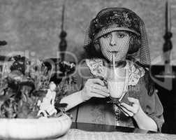 Veiled woman drinking beverage