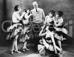Five young women dancing around a man