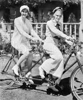 Portrait of two young women sitting on a tandem bicycle