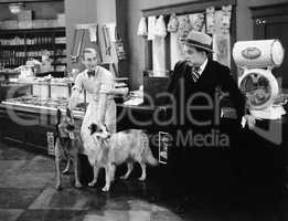 Man looking fearful at two dogs in a butcher store
