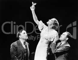 Two men supporting a woman lifting her wine glass