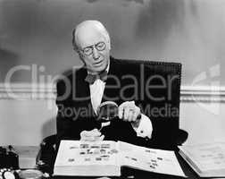 Senior man examining a postage stamp with a magnifying glass