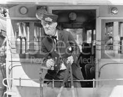 Conductor on a horse drawn streetcar holding the reins