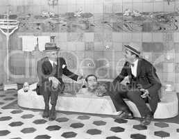 Two men sitting at the edge of a bathtub in suits and scrubbing a friends back