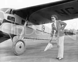 Woman in sunglasses waving a flag on the tarmac next to a airplane