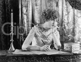 Young woman sitting at a desk with a pen in hand, looking sad while writing a letter