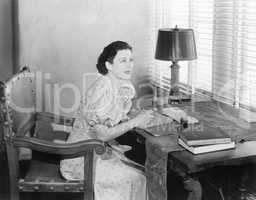 Young woman sitting at her desk writing a letter