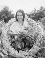 Young woman sitting in garden in a wreath of flowers
