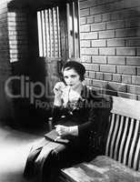 Young woman sitting n a bench in front of a jail cell