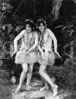 Two women dancing in grass skirts