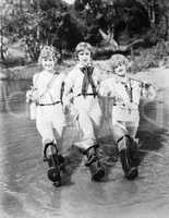 Three woman walking with fishing rods through a stream