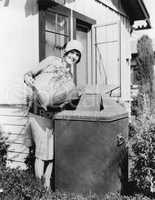 Young woman putting garbage into a garbage can