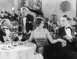 Young woman holding a man's hand at a different table while her companion is talking to the waiter