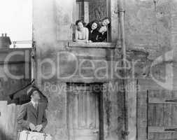 Three women looking out of a window at a man standing in the street with a suitcase