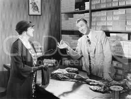 Woman buying fabric from a sales clerk at a department store