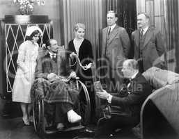 Man in a wheel chair with a broken foot and a group of people