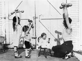 Father and his three children having a workout with dumbbells