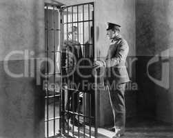 Policeman and prisoner in a jail cell