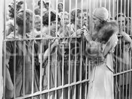 One woman standing in front of a jail talking with a group of women