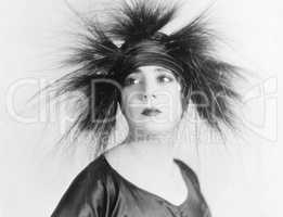 Elegant young woman looking serene in a feather hat