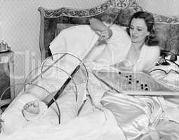 Woman in bed trying to scratch her broken foot with a pole