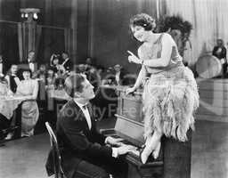 Young woman sitting on top a the piano and talking with the pianist