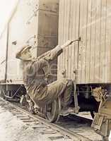 Female hobo climbing freight train