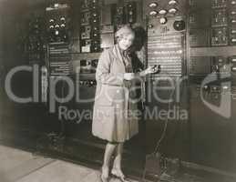 Woman monitoring sound in 1930s recording studio