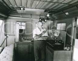 Man preparing tea inside his camping trailer
