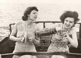 Two women having a snack on motorboat