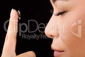 Closeup of woman putting contact lenses