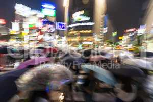 Motion Blurred People in Rain on Shibuya Crossing, Tokyo, Japan