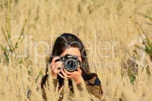 Nature photographer girl in yellow field
