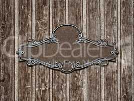Vintage cast metal plate on old wooden texture close-up