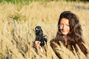 Girl nature photographer waiting in autumn meadow
