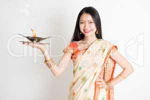 Girl with Indian sari dress holding oil lamp diya