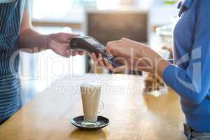 Customer making payment through payment terminal at counter in caf�©
