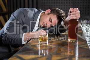 Drunk man lying on a counter with bottle of whisky