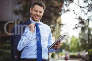 Handsome businessman holding dairy and blazer