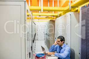 Technician talking on mobile phone in server room