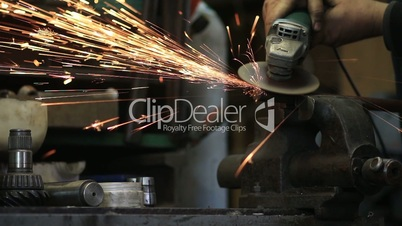 Worker cutting metal with a grinder