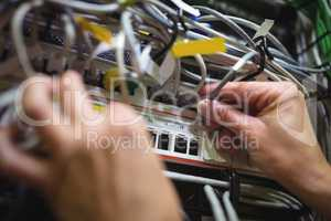 Technician plugging patch cable in a rack mounted server