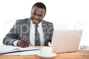 Happy businessman working at office desk